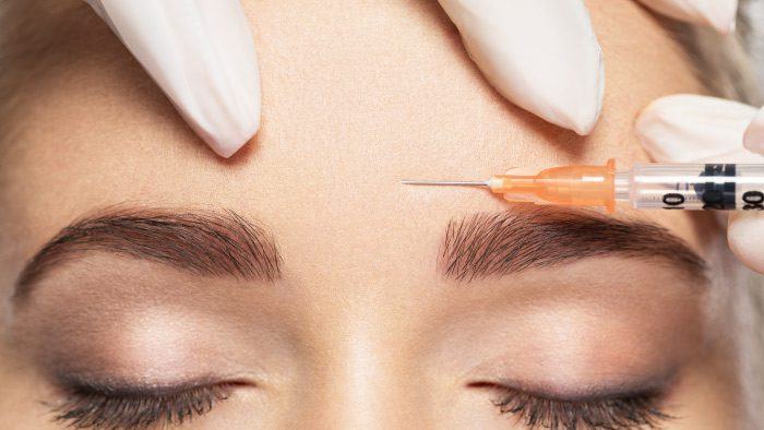 Botox being injected into the forehead.