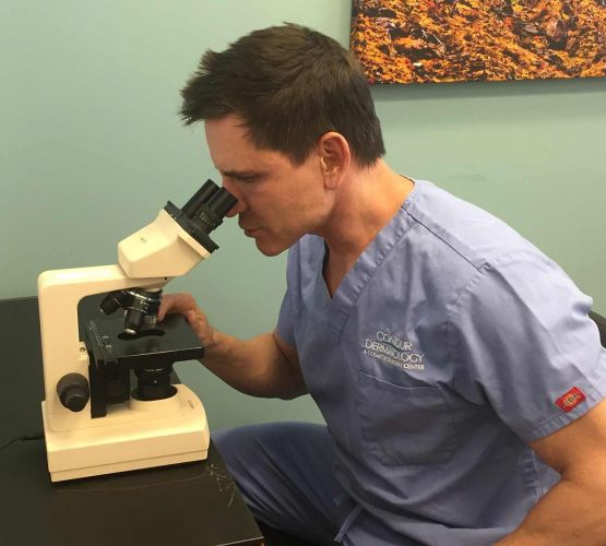 Dr. Jochen reviewing a MOH's surgery sample to determine if it is cancerous.